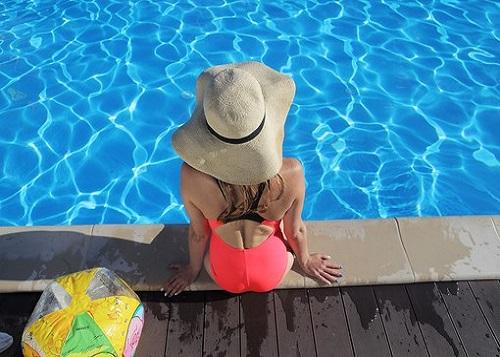 プールサイドの帽子の女性