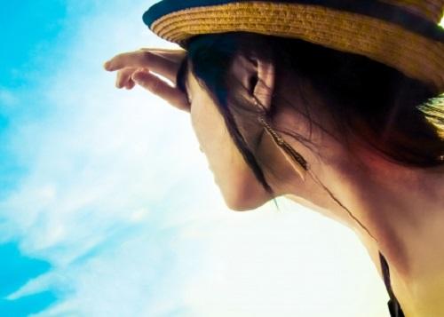 日差しを遮る女性