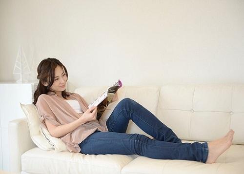 ソファで雑誌を読む女性