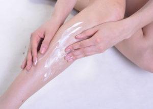 脚にクリームを塗る