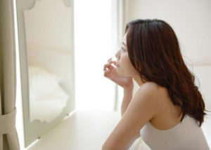 鏡を見る20代女性